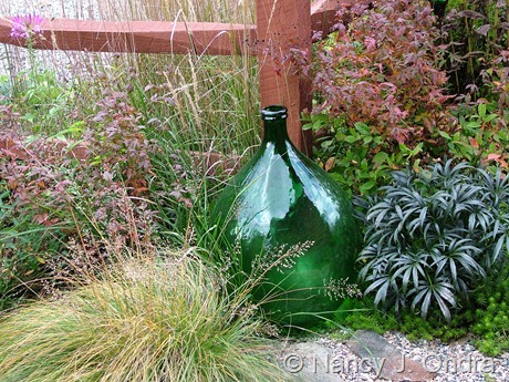 Green glass carboy (demijohn) in garden at Hayefield